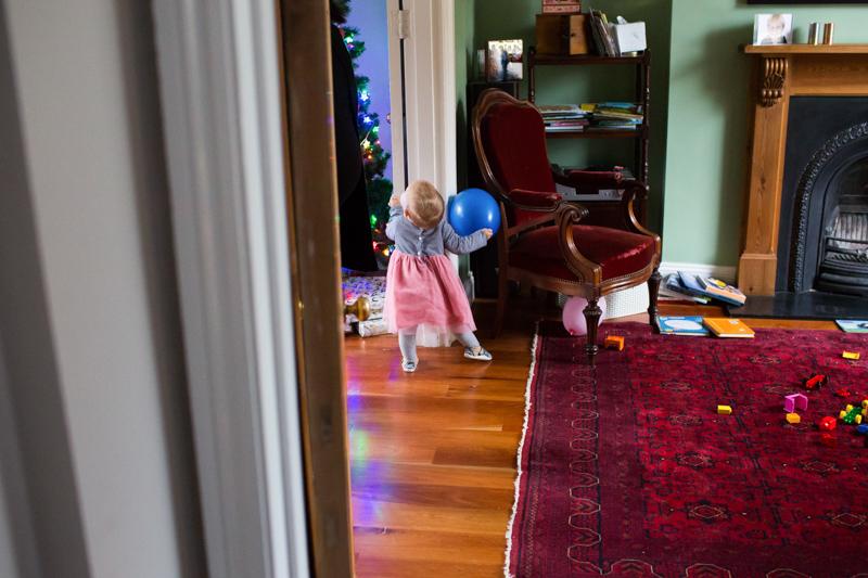 Baby girl looking at Christmas tree.