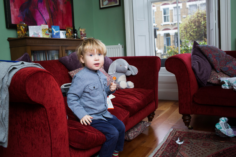 Little boy smiling on red sofa.