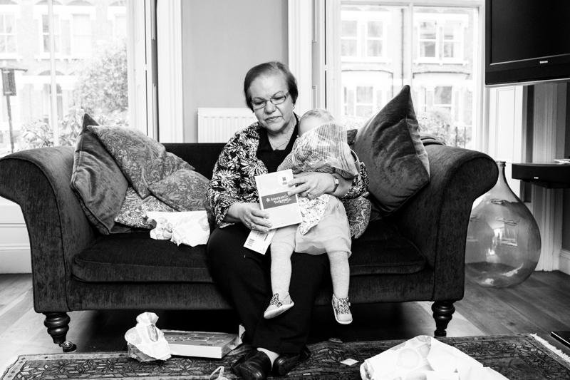 Lady holding baby on sofa.