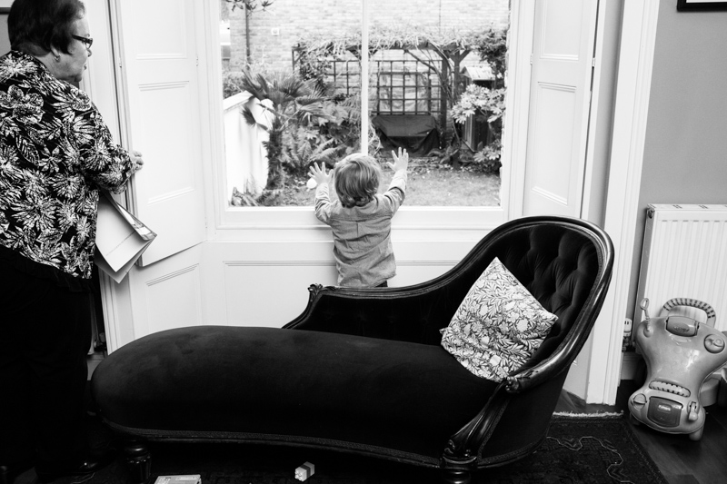 Little boy looking at of window with lady looking on.