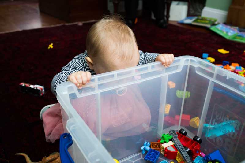 Baby girl looking into toy box.