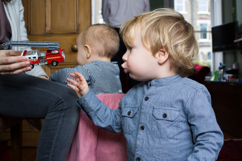 Boy looking at toy fire engine