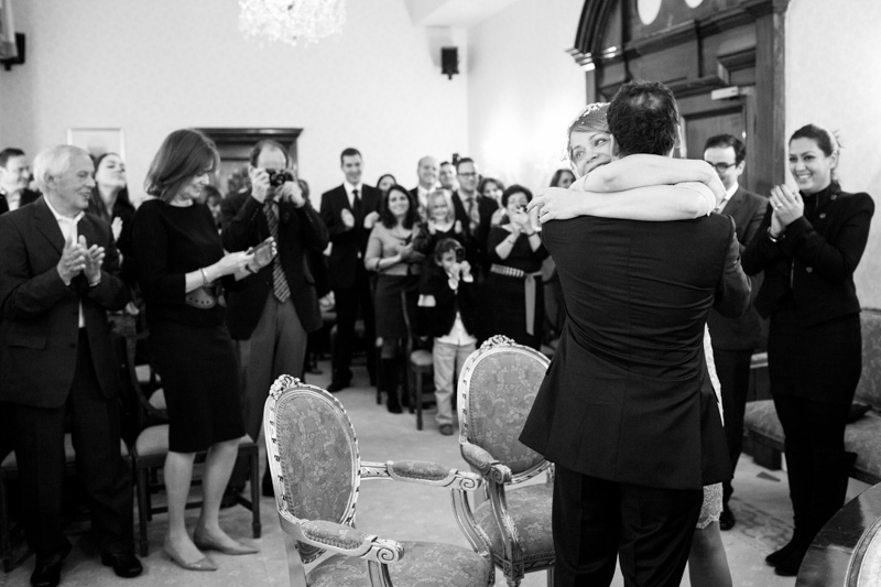 Wedding couple hugging in wedding ceremony with guests in background.
