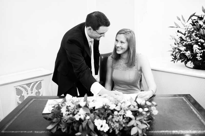 Couple looking at each other and signing the register.