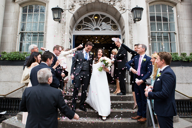 Bride and groom walking down steps of Chelsea Old Town Hall with guests throwing confetti on them.