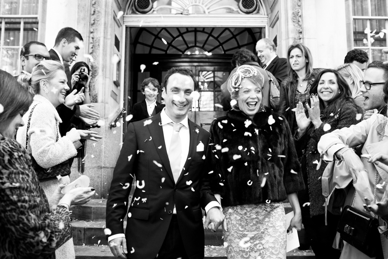 Bride and groom laughing with confetti being thrown on them.