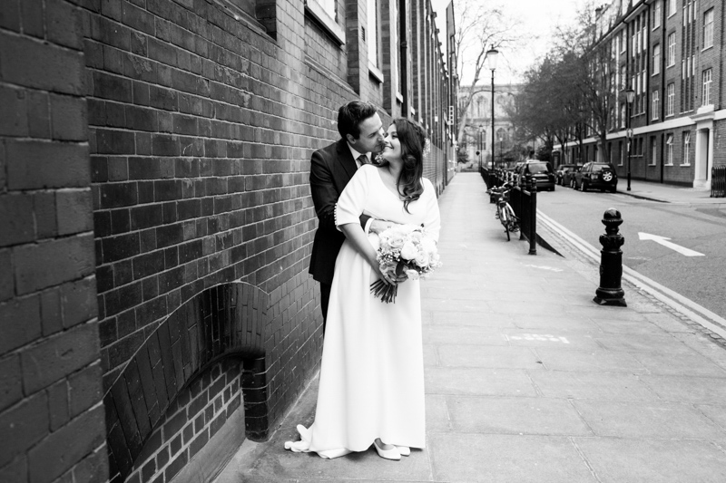 Bride and groom looking at each other next to a brick wall.