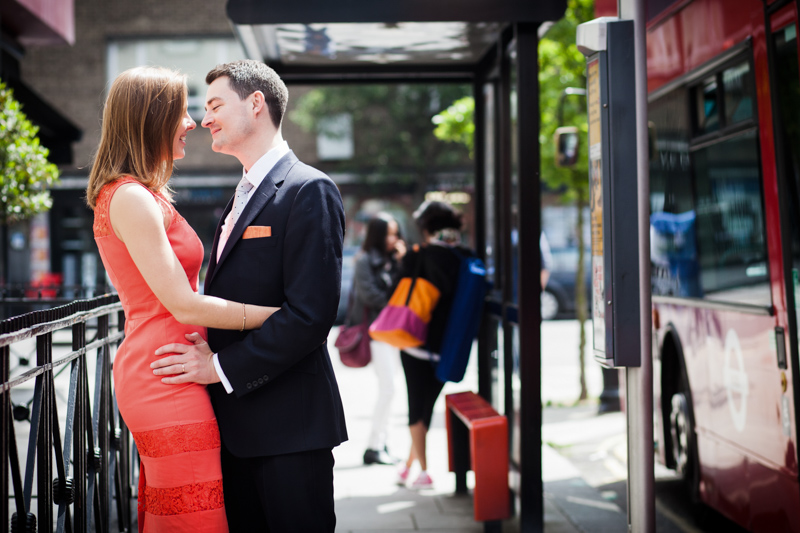 Man and lady in orange dress looking at each other next to bus and bus stop.