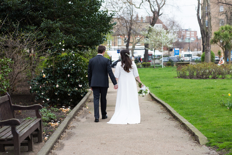 Wedding couple walking hand in hand past grass and shrubs.