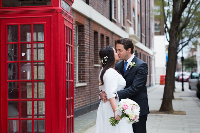Wedding couple kissing with phone box in the background.