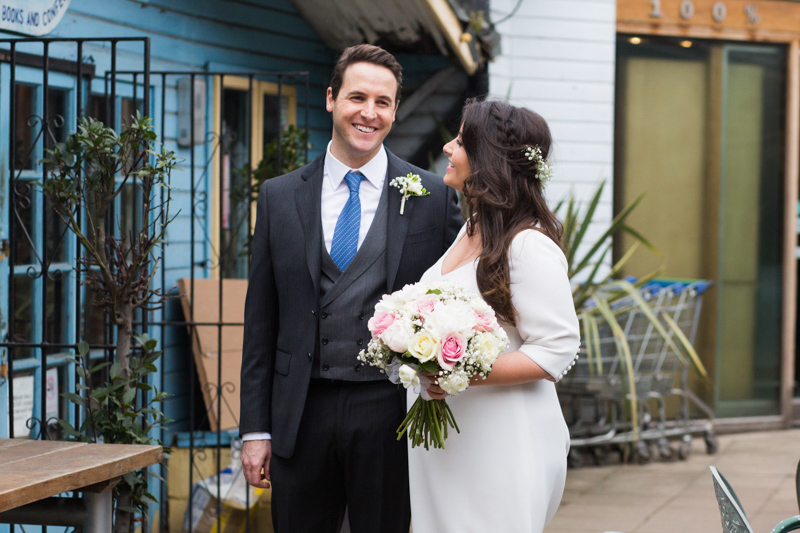 Bride and groom looking happy in front of blue building.