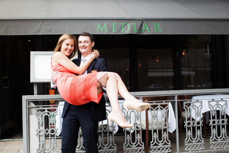 Man holding a lady in an orange dress in front of Medlar Restaurant.