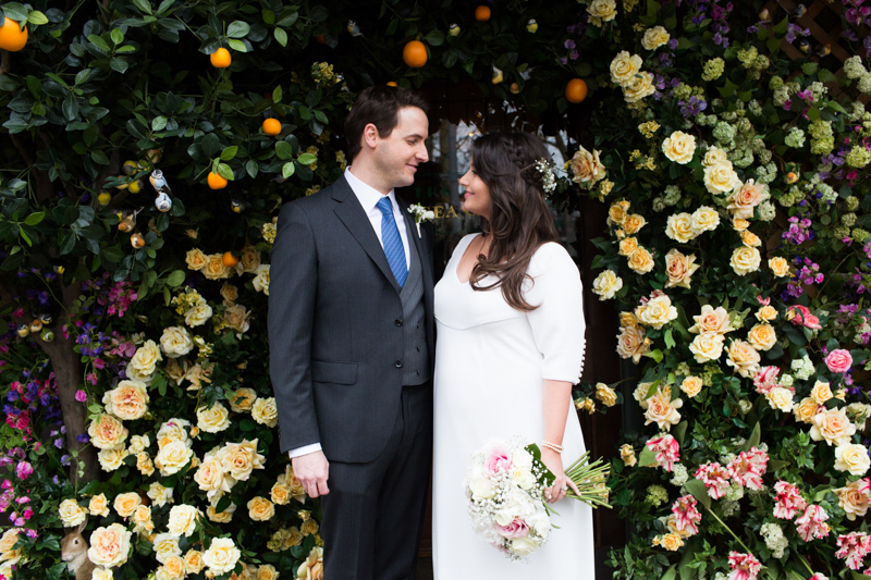 Bride and groom looking at each other in front or archway of flowers.