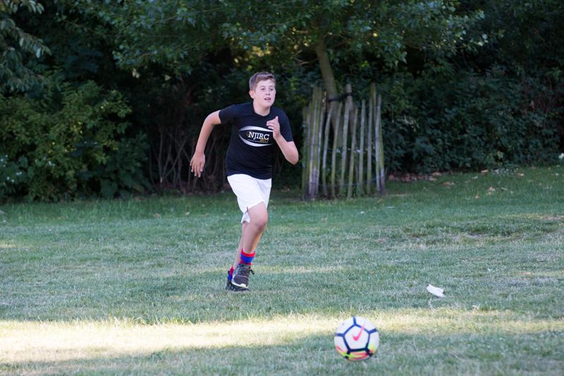 Boy running towards football.