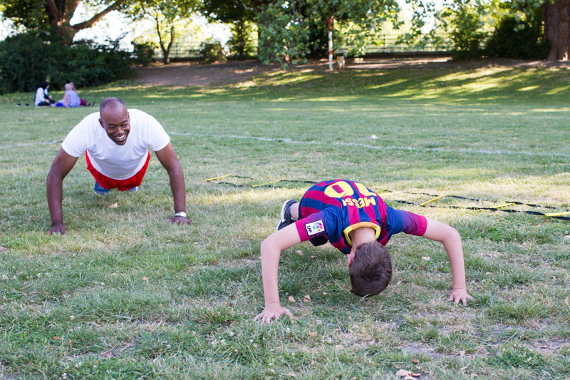 Boy doing press-ups on the grass with man looking on.