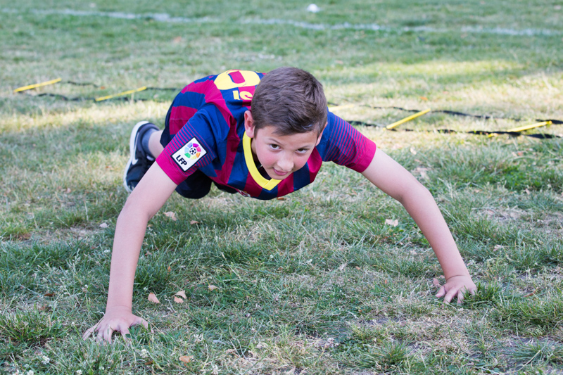 Boy doing push-ups on the grass.