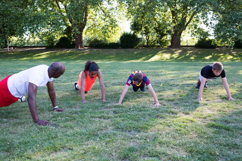 Three children and a man doing press-ups on the grass.