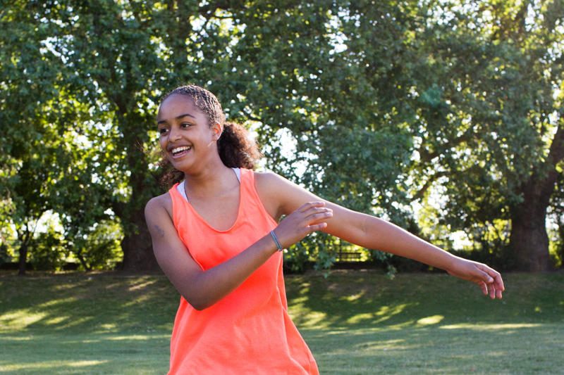 Girl in orange top swinging her arms.