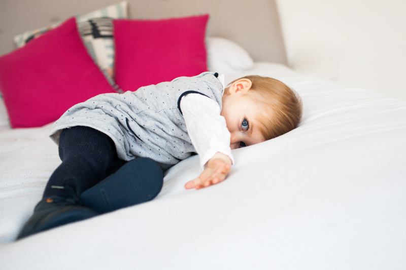 Baby lying on bed with pink cushions behind her.