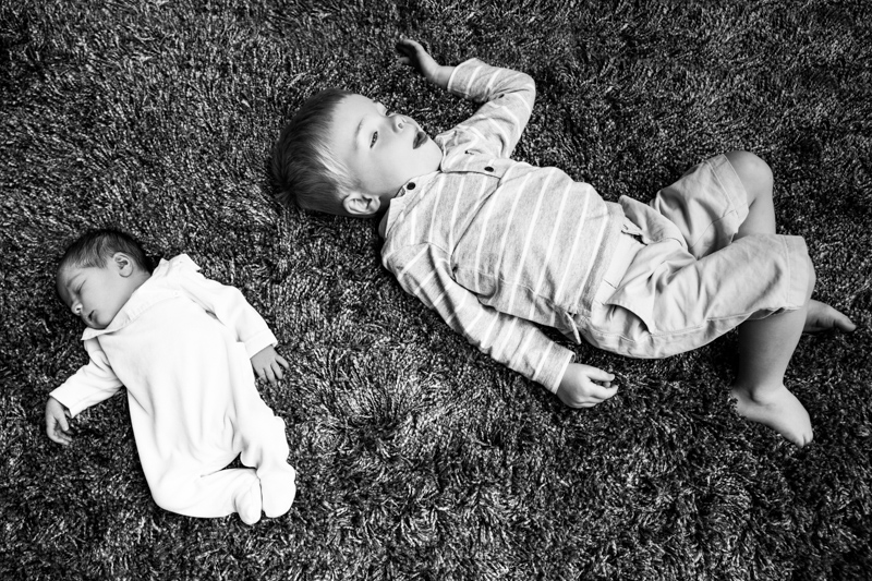 Newborn baby and his older brother lying on a dark coloured rug.