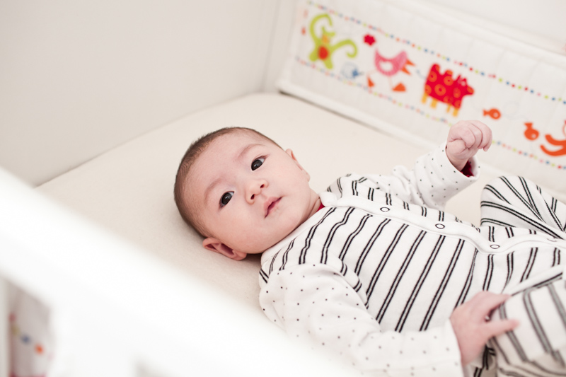 Baby in cot with lovely colours behind him.