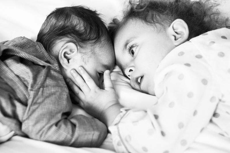 Little girl touching the face of her baby brother.
