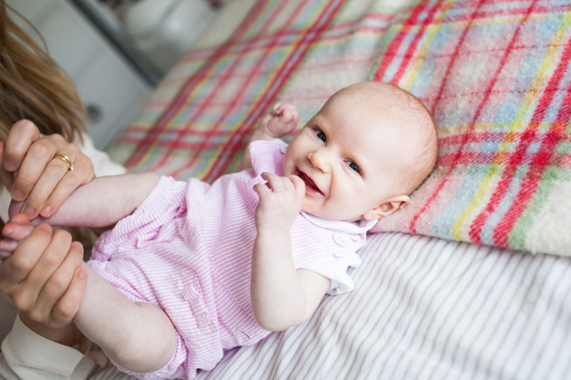 Very smiley baby in pink outfit with patterned blanket behind her.