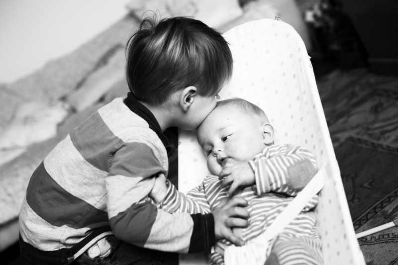 Little boy kissing his baby brother in his chair.