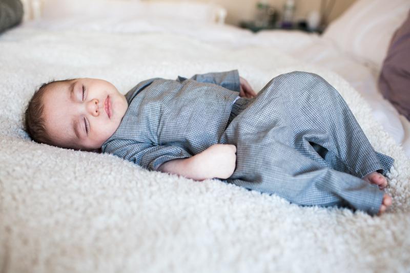 Baby in blue pyjamas lying asleep on a bed.