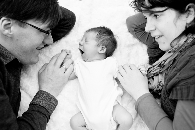 Baby yawning on white blanket with his parent's looking at him.