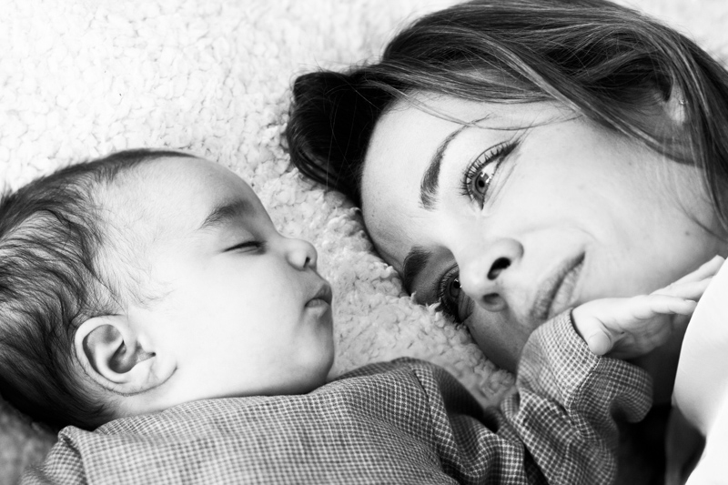 Mother looking lovingly at her asleep baby.