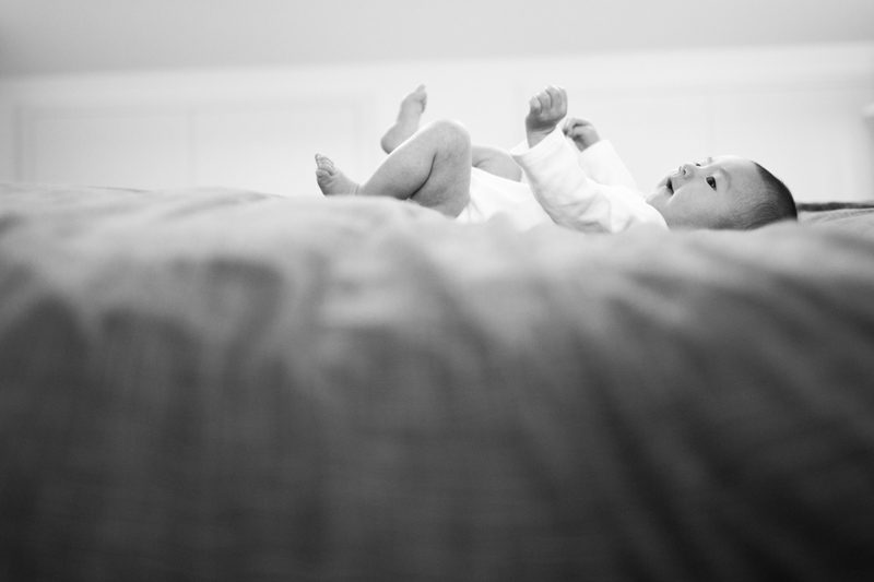 Boy with arms and leg in the air lying on the bed.