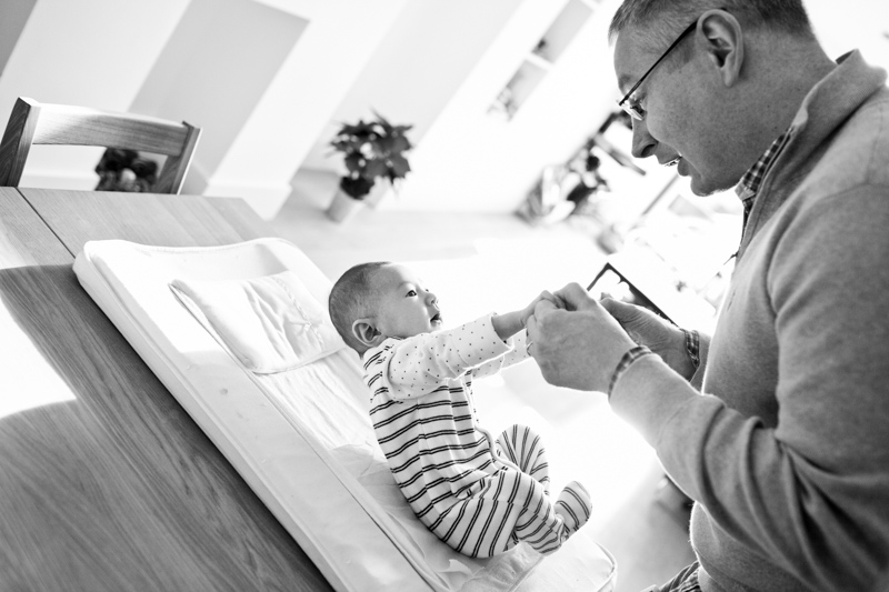 Dad lifting his baby off changing mat.