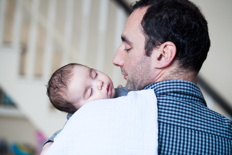 Man looking at sleeping baby on his shoulder.