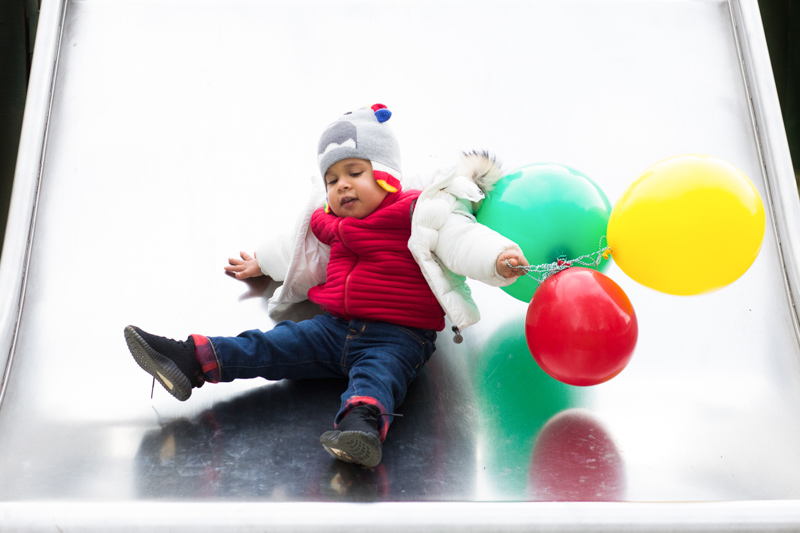 Baby wearing a hat going down a slide with a red, green and a yellow balloon.