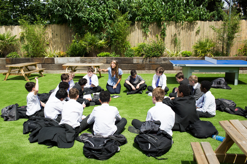 A female teacher teaching boys outside, sitting on grass