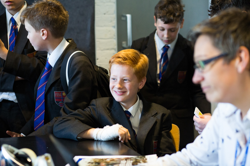 School boy smiling and surrounded by other pupils.