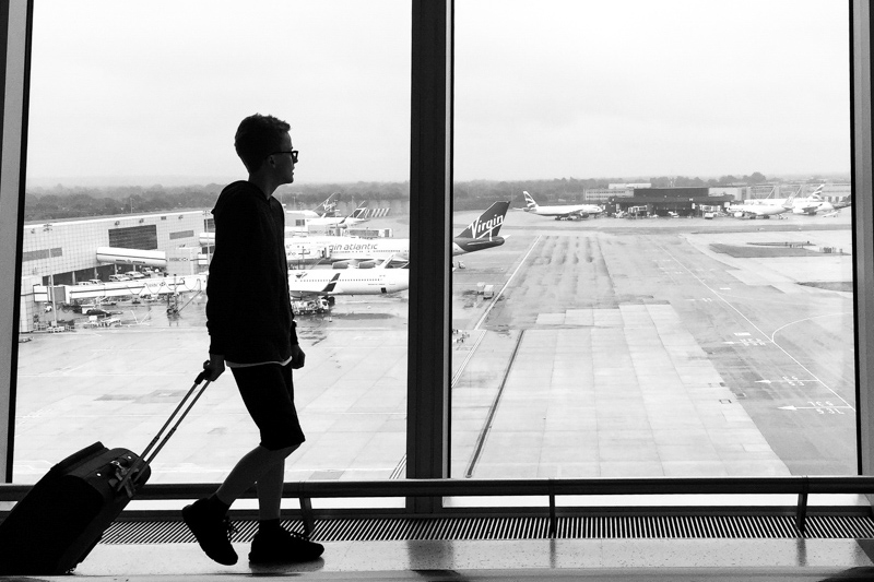 Teenage boy walking with suitcase in front of airplanes.