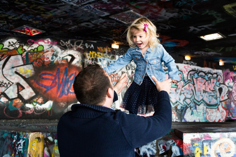 Girl jumping into man's arms with graffited wall in the background.