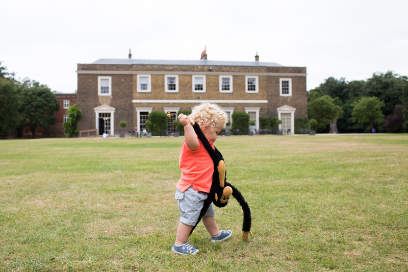 Little boy in orange top carrying toy monkey walking in front of Fulham Palace.