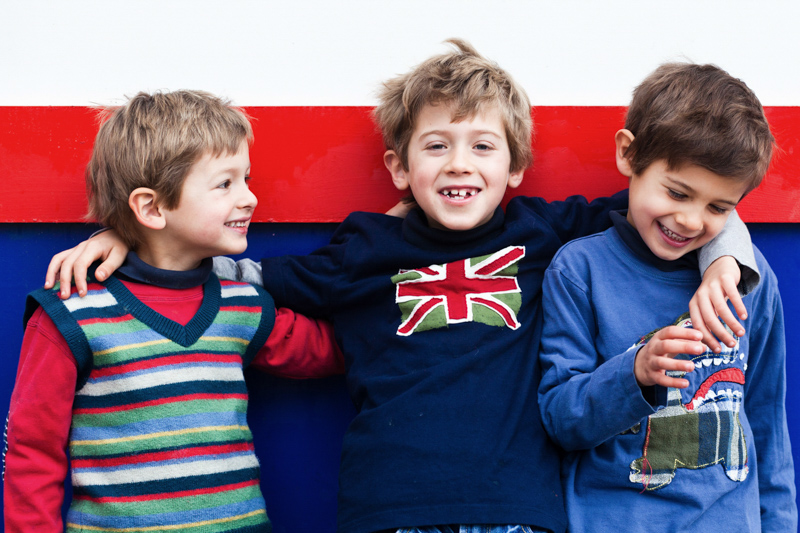 Three boys in front of red, white and blue wall.