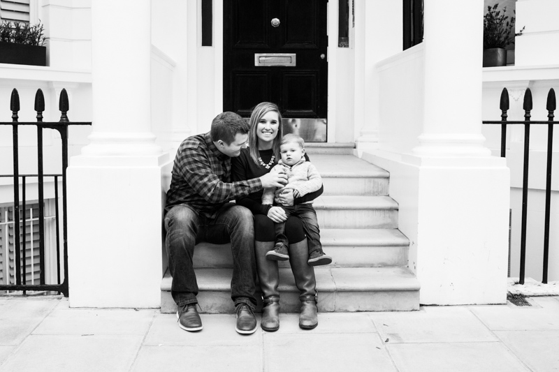 Couple with baby sitting on steps in front of large door.