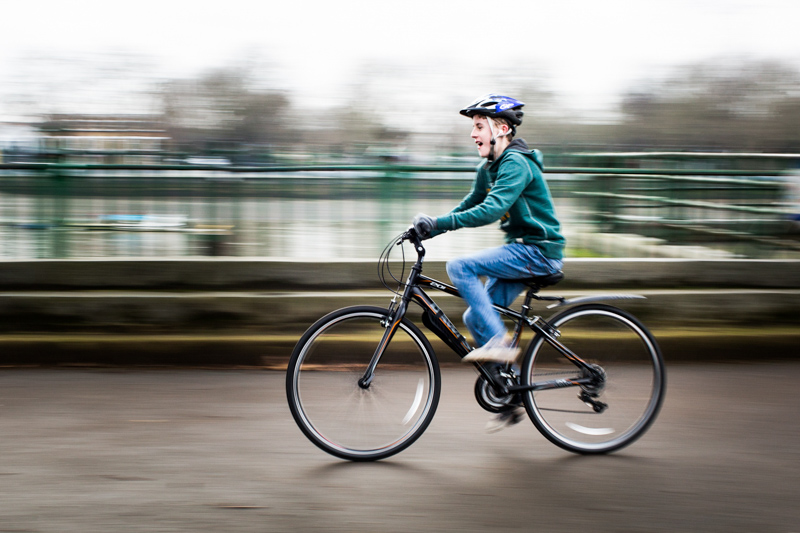 Boy in green top riding a bicycle.