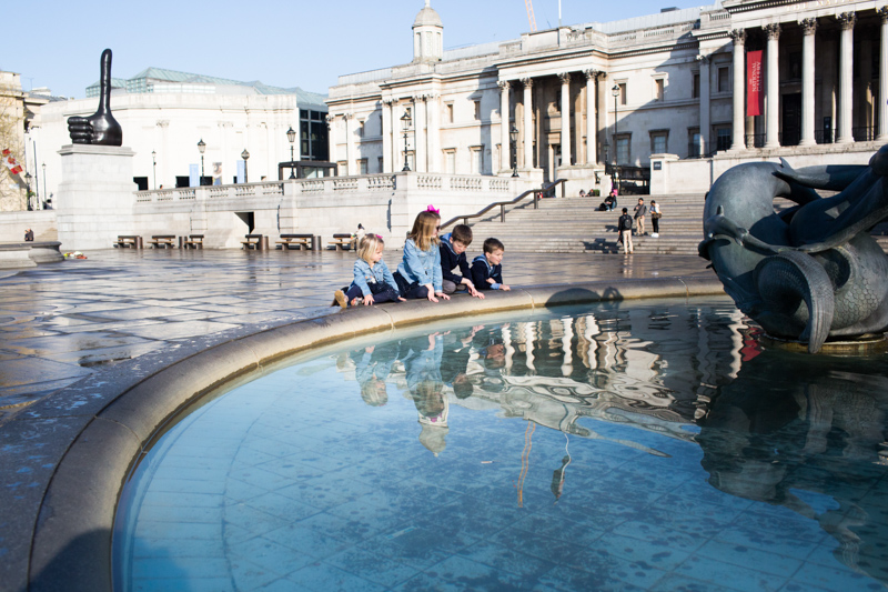 Four children looking at fountain in Trafalgar Square with the National Gallery in the background.