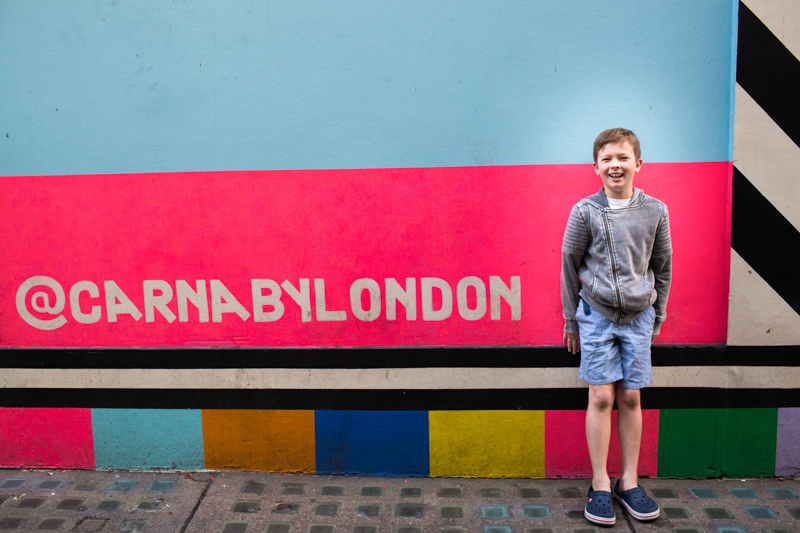 Laughing boy next to Carnaby by London sign.