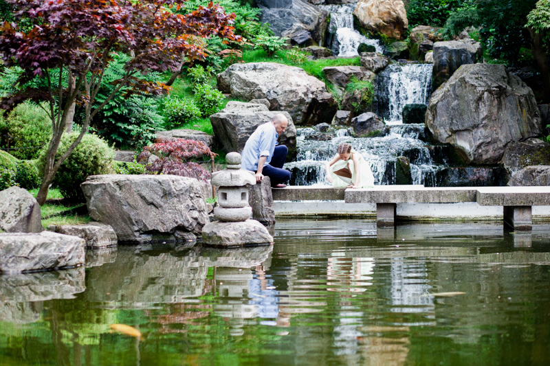 Man and girl in front of waterfall looking in pond.
