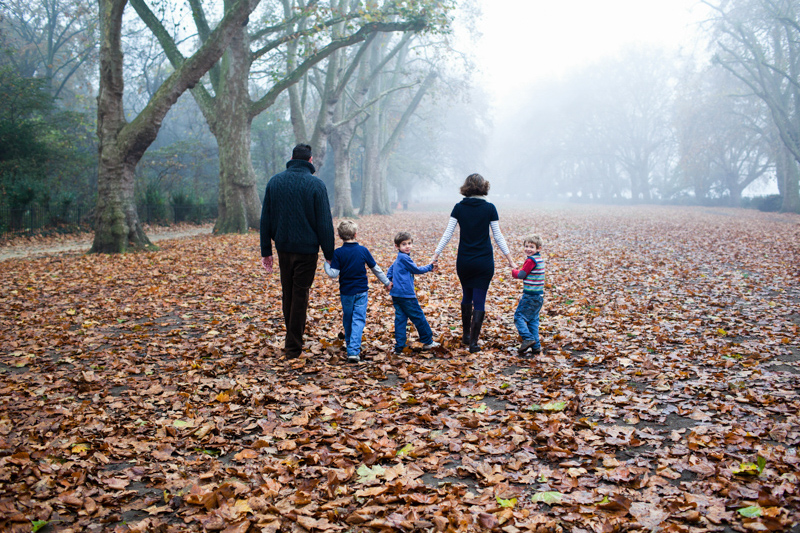 Family of five walking away across Autumn leaves.