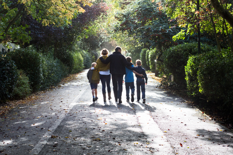 Family of five walking away through park.