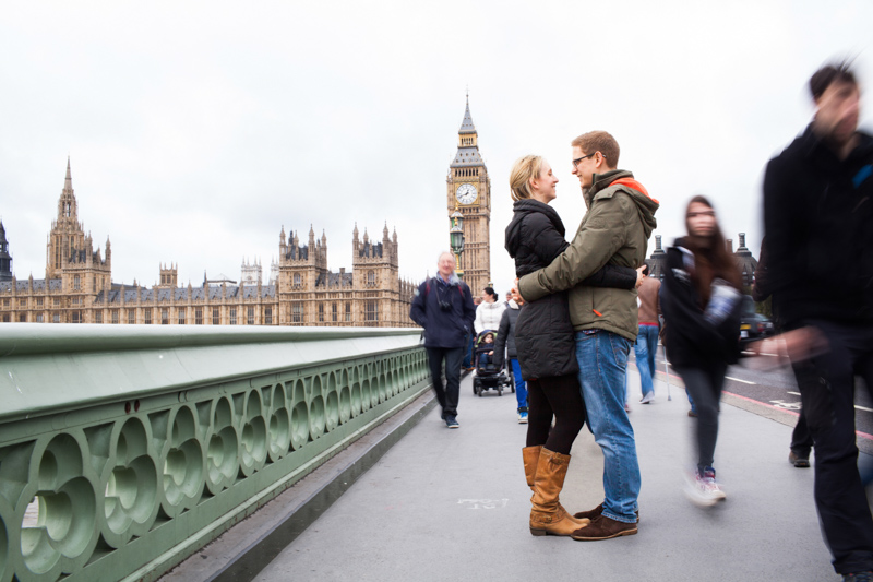 Man and lady hugging on Westminster Bridge with the Houses of Parliament in the background and people rushing by