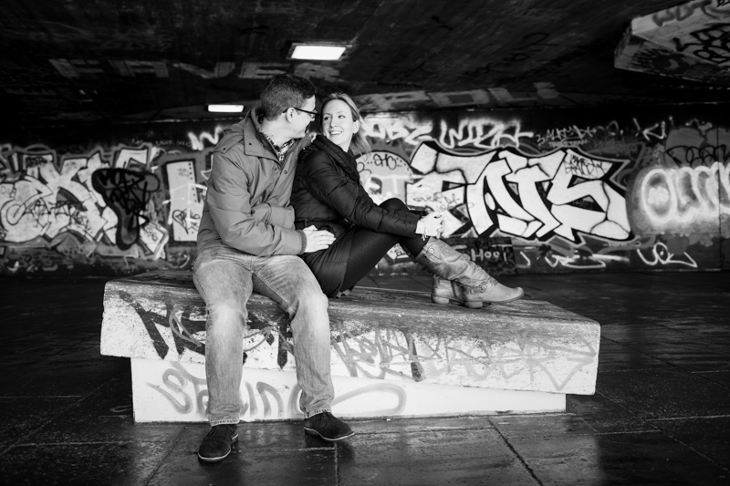 Couple with graffiti behind them.